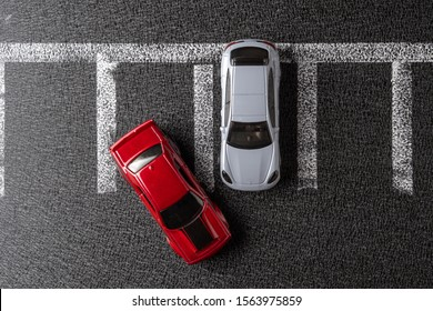 Odessa, Ukraine - November 17, 2019: Two toy cars in the parking lot. Top view