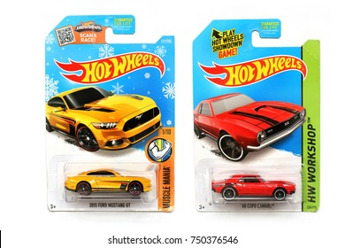 Odessa, Ukraine - November, 2017: A copy of the Ford Mustang GT and  Copo Camaro car. Hot Wheels. Kids toys. Machines. Toys on a white background. Close-up. Red Chevrolet Camaro