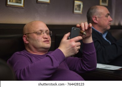 Odessa, Ukraine November 24, 2017: Elegantly dressed men smoking cigars in a luxurious cigars club during cigar party, drink alcohol