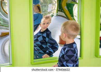 Odessa, Ukraine - OCT 24: A boy playing with distorted mirror in museum of science while school excursion