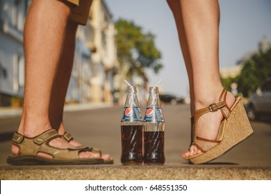 ODESSA, UKRAINE - OCTOBER 15, 2014: Close up of woman feet standing on tiptoe while kissing with man outdoors summertime. Pepsi in glass bottles with straw is standing between a couple