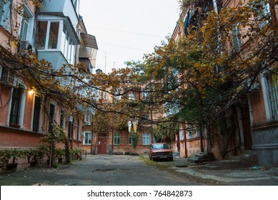 ODESSA, UKRAINE - OCTOBER 15, 2017: Old typical soviet courtyard of Odessa with grape vines and a red car in the autumn evening.