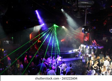 Odessa, Ukraine - October 2, 2011: A large crowd of people having fun in a nightclub at a concert during creative light and music show. Cheerful young people, candy and smoke on club party. authentic