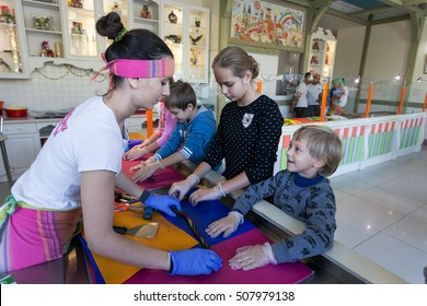 Odessa, Ukraine - October 28, 2016: Children in workshop at candy store with their hands learn to make chocolates under guidance of an master. Hand made chocolates. Child development in candy store