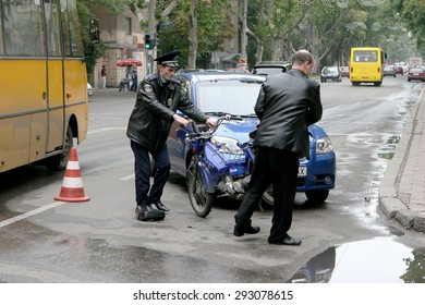 Odessa, Ukraine - October 4, 2008: Light accident between a car and a motorcycle. Bike crashed into a car. He lost control on the wet asphalt. Powered Police