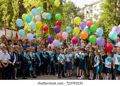 ODESSA, UKRAINE September 1, 2017: School line is in schoolyard with pupils and teachers. Children go back to school. Knowledge Day, first day of school.  First-graders sit in class