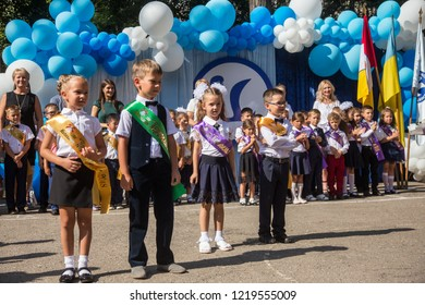 ODESSA, UKRAINE September 1, 2018: September 1, day of the celebration of knowledge. Smiling happy first graders and their happy parents. Teacher in schoolyard holiday Beginning of the training year