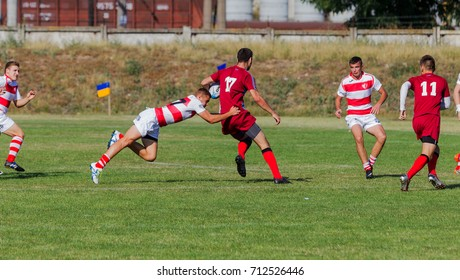 ODESSA, UKRAINE - September 10, 2017: International rugby tournament between teams Chisinau - Moldova and Odessa - Ukraine. Fragment of tight rugby game on green grass field