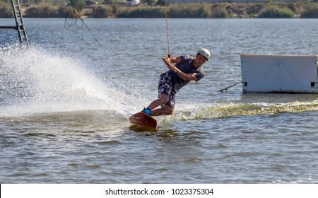 ODESSA, UKRAINE - September 17, 2017: Wake Park. Summer beach water sports. The athlete glides on water on board. Skate on water. Skateboarding, Wakeboarding. Summer information sport background