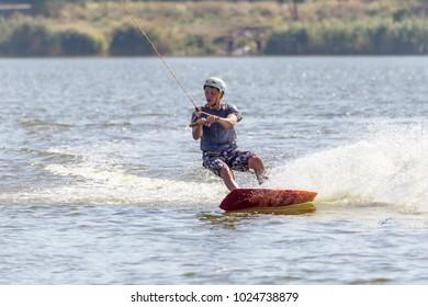 ODESSA, UKRAINE - September 17, 2017: Wake Park. Summer beach water sports. Unknown Athlete slides on water on board. Skates on water. Skateboarding, Wakeboarding. Summer information sport background