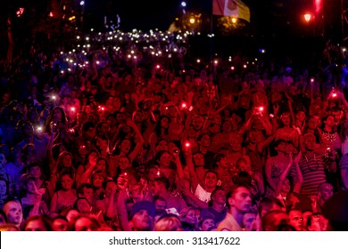 Odessa, Ukraine - September 2, 2015: The audience at concert during the creative light and music show fashionable jazz orchestra. Night scene, audience emotionally watching, standing outside on stairs