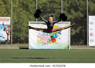 Odessa, Ukraine - September 2, 2015: Bright dynamic characteristics of a support group of women's sports team. Performance Support Group. Bright beautiful young girl in sports dance form on playground