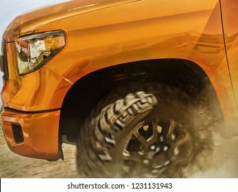 Odessa, Ukraine- September 2, 2018: Moving offroad orange Toyota Tundra wheel and bumper view.
