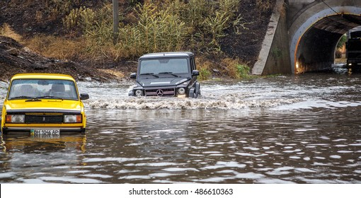 ODESSA, UKRAINE - September 20, 2016: Cars driving on a flooded road during flooding caused by torrential rains. Cars float on water flooded streets. The disaster on the city streets