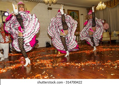 Odessa, Ukraine - September 4, 2015: Beautiful sexy girls from the dance ensemble in bright beautiful dress dancing French cancan at the banquet in the restaurant.