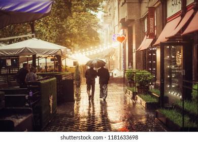 ODESSA, UKRAINE September 6th, 2018: Two men go with an umbrella in the rain