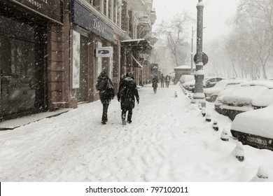 ODESSA, UKRAINE-January 16, 2018: Strong snowfall, cyclone in city streets in winter. Cars are covered with snow. Slippery road. Bad weather in winter: heavy snow and snowstorm. Pedestrians go on snow