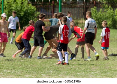 ODESSA, UKRAINE-May 6,2017: brutal rugby fight between children's teams. Children boys Players hard grasp opponents in fight for ball in rugby. Boys Rugby players seize each other in dispute over ball