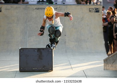 ODESSA-24 AUGUST,2017: Aggressive In-Line skating contest in outdoor skatepark on extreme sports event.Young athletes ride on roller blades on summer festvial.Skter girl grinds on rail in skatepark
