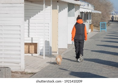 Odessa,Ukraine - Jan 02,2021 Morning walk of a lady with a dog along the embankment.