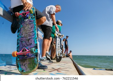 ODESSA,UKRAINE-2 AUGUST,2017:Scratched old skateboard deck in hands of young skater boy.Skateboarding contest in summer.Extreme sport competition background.Skating board with graffiti drawing