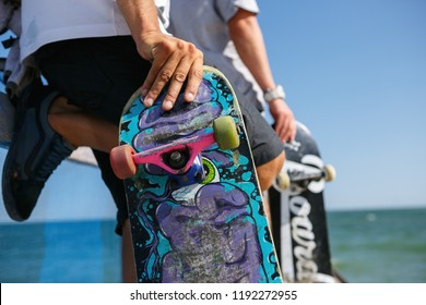 ODESSA,UKRAINE-21 AUGUST,2017: Skater boy holds old skateboard in hands on mini ramp in outdoor skatepark.Extreme summer sports competition background.Popular extremal sport.Skate board deck close up