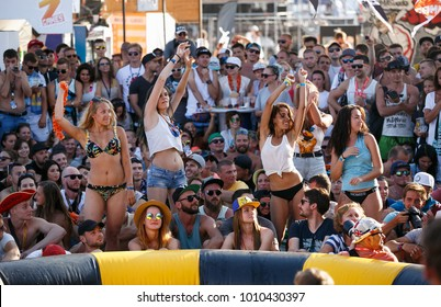 ODESSA,UKRAINE-21 AUGUST,2017:Four pretty young girls in swim wear bikinis dancing in the crowd on beach party at summer youth festival in Europe