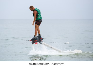 ODESSA,UKRAINE-21 AUGUST,2017:Young man riding on hydroflyer hover board in sea.Trendy fly board jetboots on feet.Modern turbojet hovering board powered with aqua scooter craft