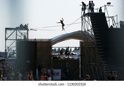 ODESSA,UKRAINE-21 JUNE,2017: Young girl walks on rope high above ground.Slackline contest on the beach.Strong people take part in slack line walking competition walking on tightropes on seaside