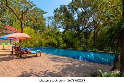 Odisha/ India - March 15,2020. An infinity Swimming pool with chairs with umbrella in a Indian resort.