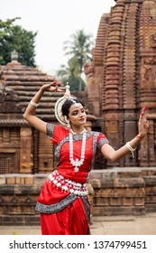 Odissi dancer looks at the mirror posing in front of a Temple, Bhubaneswar, Odisha, India