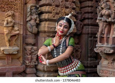 Odissi dancer striking pose against the backdrop of Mukteshvara Temple with sculptures in bhubaneswar, Odisha, India