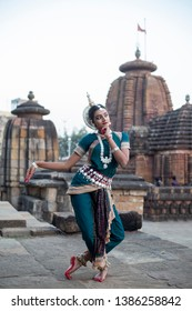 Odissi dancer striking pose against the backdrop of a temple with sculptures in bhubaneswar, Odisha.