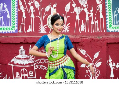Odissi dancer striking a pose infront of wall Street Art (Pattachitra) at Bhubaneswar, Odisha, India