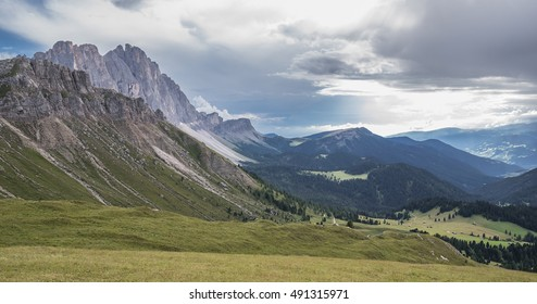 Odle mountain massif and Funes valley below as seen from the alpine pasture of Genova refuge on a cloudy, before-rain early evening, Dolomites, Trentino, Alto-Adige, South Tyrol, Italy