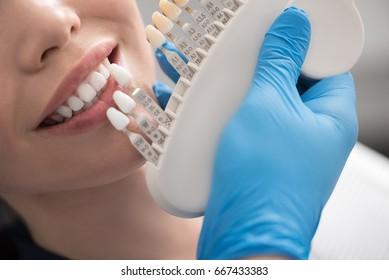 Odontologist selecting dental crown for beaming female
