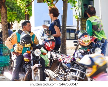 Oeiras, Brazil - Circa June 2019: Motorcycle taxi drivers talking to a client in the historic center of Oeiras