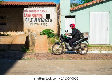 Oeiras, Brazil - Circa May 2019: Older man riding his motorcycle using a plastic beer crate as a motorcycle trunk