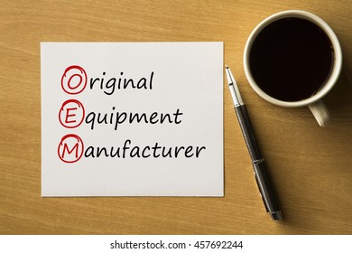 OEM Original Equipment Manufacturer - handwriting on paper with cup of coffee and pen, acronym business concept