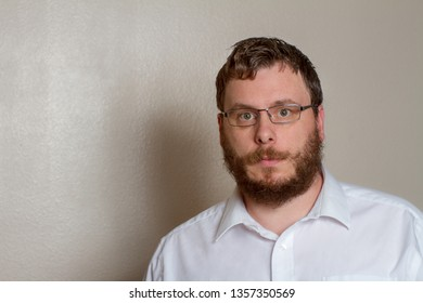 Off center bearding man wearing glasses looking at the camera while wearing a button up shirt