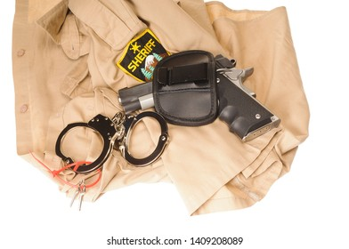 Off duty Deputy's equipment, computer, handcuffs, pistol, badge, and shirt isolated on white