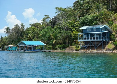 Off grid waterfront home on lush tropical coast with boat at dock on an island of the archipelago of Bocas del Toro, Panama