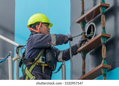 Off Itajai, Santa Catarina / Brazil - 09 28 2019: A seaman wearing hard hat and life jacket secures the pilot ladder to the ship's hull so that the pilots can safely disembark.