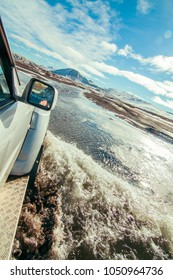 Off road action adventure traveler, 4 wheel drive 4x4 driving with a big splash through water in the Iceland, snow covered mountains in the background, blue sky