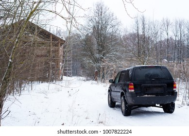 Off road black vehicle in the forest near old building on winter snow
