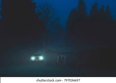 Off road car with headlights on in misty forest near old barn at dusk.