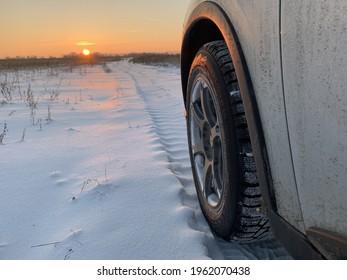 Geländewagen auf der Winterstraße. Sonnenuntergang. Leerzeichen kopieren