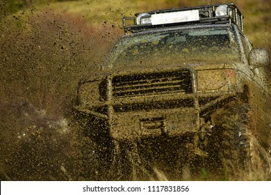 Off road car takes part in racing on nature background. Splash of dirt under SUV on countryside road. Cross country rallying or rally raid. Extreme and four wheel drive concept