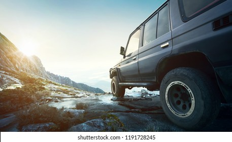 Off road travel concept with 4x4 car at sunset and mountains view