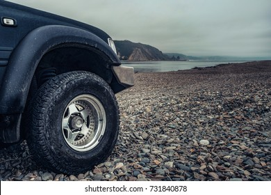 off road traveling by car adventure wildlife, scientific expedition or extreme travel on a SUV automobile,wheel of an SUV on a background of a mountain landscape